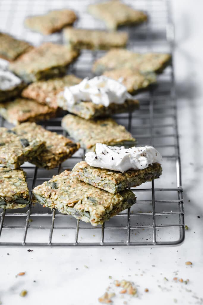 nut free keto crackers resting on a cooling rack with 2 crackers with fresh mozzarella close up shot