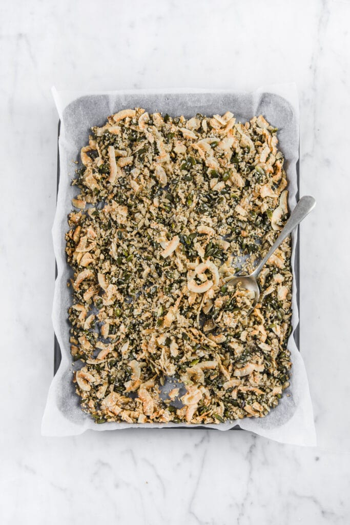overhead shot of nut free keto cereal spread on a grease proof lined baking sheet
