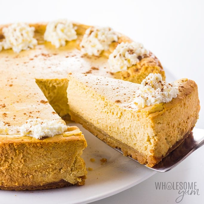 low carb keto pumpkin cheesecake with one slice serving being lifted with a cake slicer