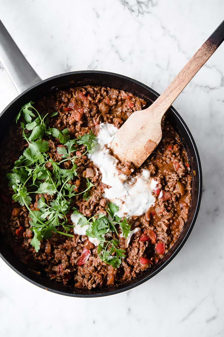 close-up overhead shot of keto chili con carne on a pan topped with sour cream with a wooden spoon atop a marble kitchen counter