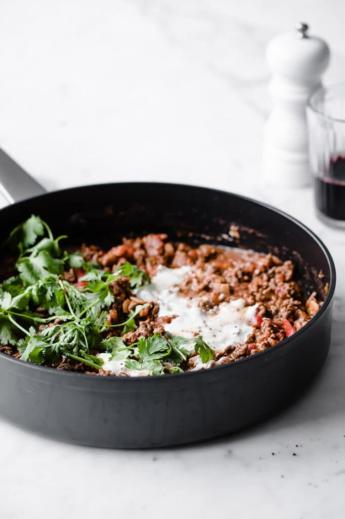 close-up shot of keto chili con carne on a pan topped with sour cream atop a marble kitchen counter