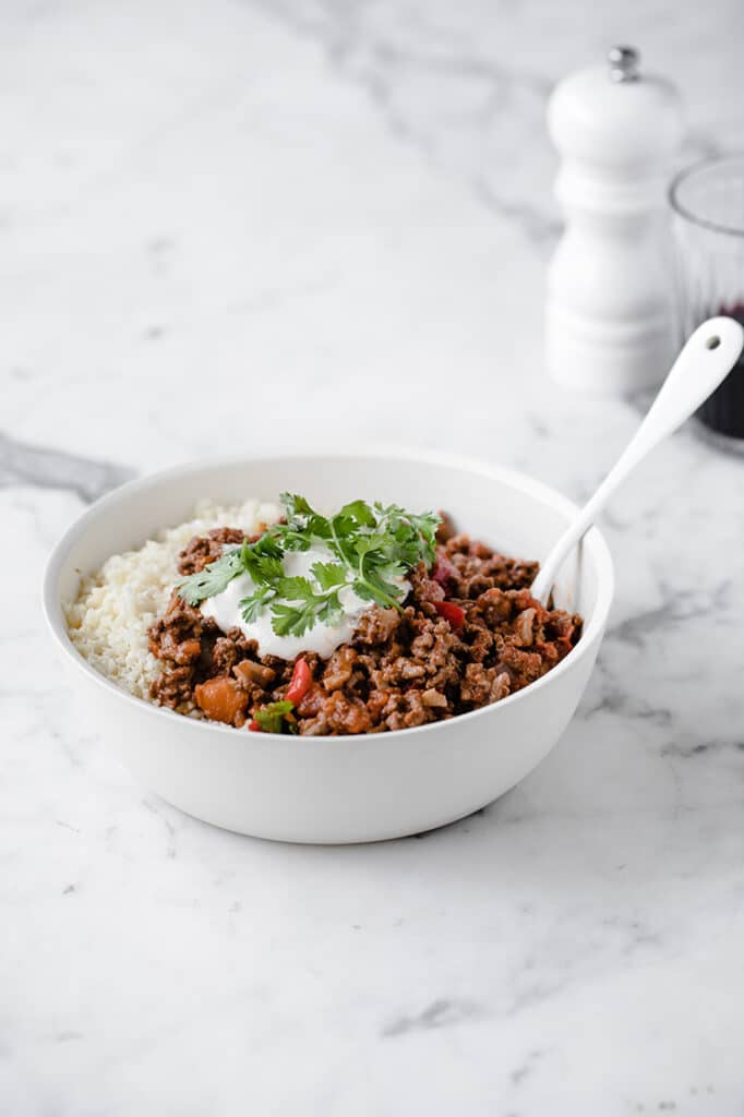 angled shot of a bowl of keto chili con carne and cauliflower rice atop a marble kitchen counter