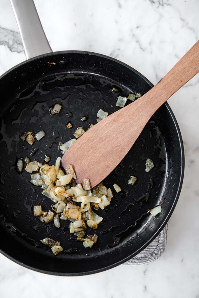 chopped onions being sautéed in olive oil on a large pan
