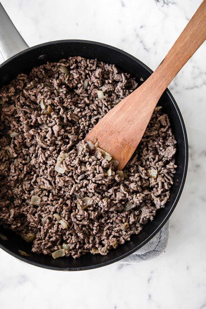 sautéed ground beef beeing stirred with a wooden spoon on a large pan