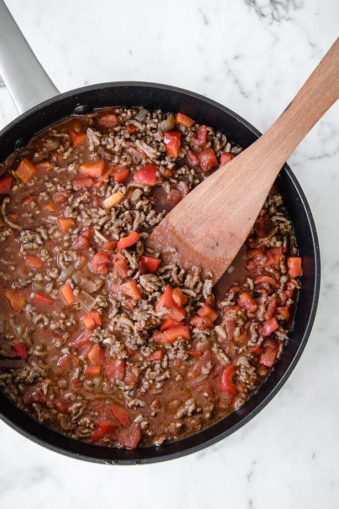 tomato puree poured over ground beef while being stirred in a large pan with a wooden spoon
