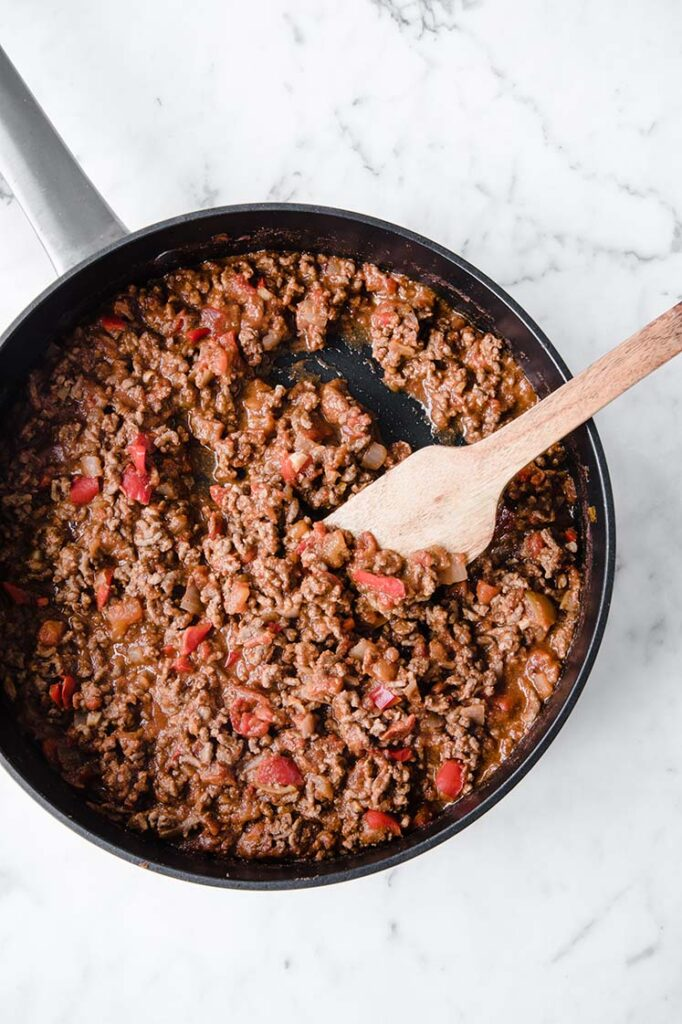 keto hili con carne being simmered until sauce thickens while being stirred with a wooden spoon in a large pan atop a marble kitchen counter