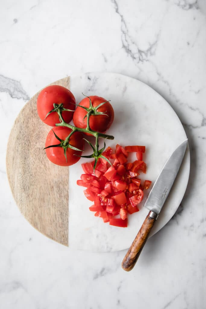 3 whole tomatoes and some diced tomatoes on a chopping board with a knife at the side atop a marble kitchen counter