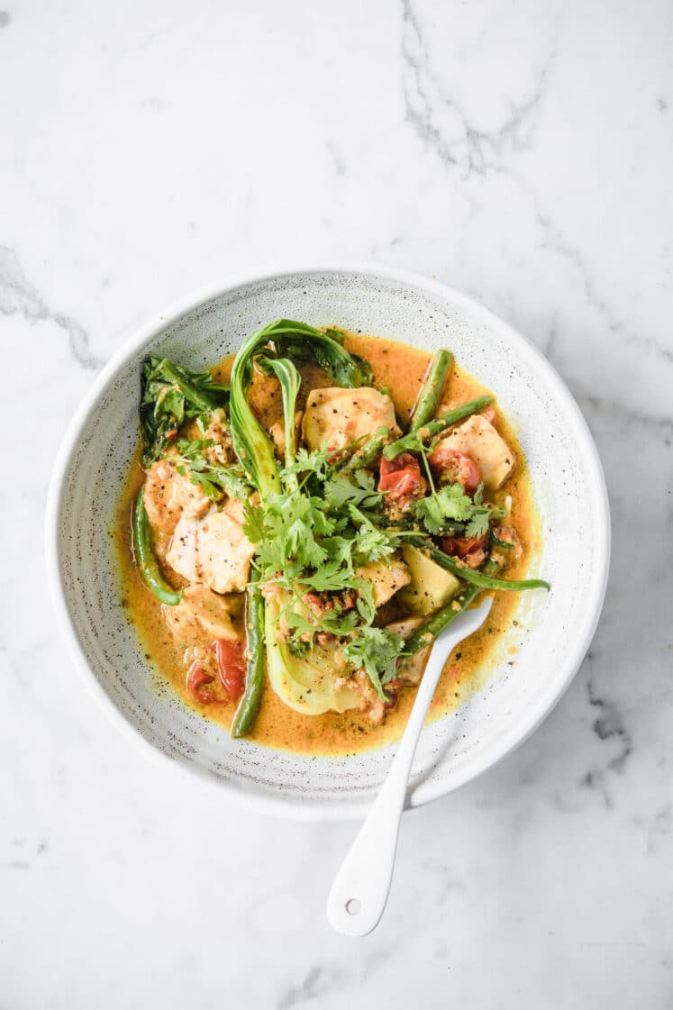 Keto Salmon Coconut Curry: a bowl of Low-Carb Salmon Curry with a fork atop a marble kitchen counter