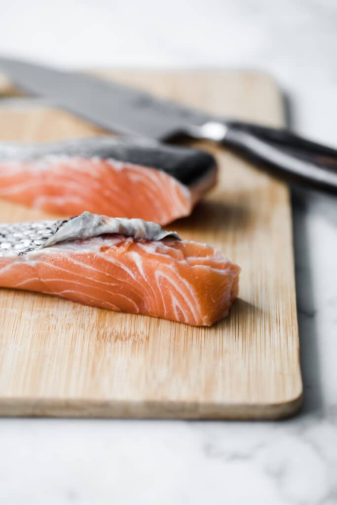2 cuts of salmon, skin being removed, on a chopping board