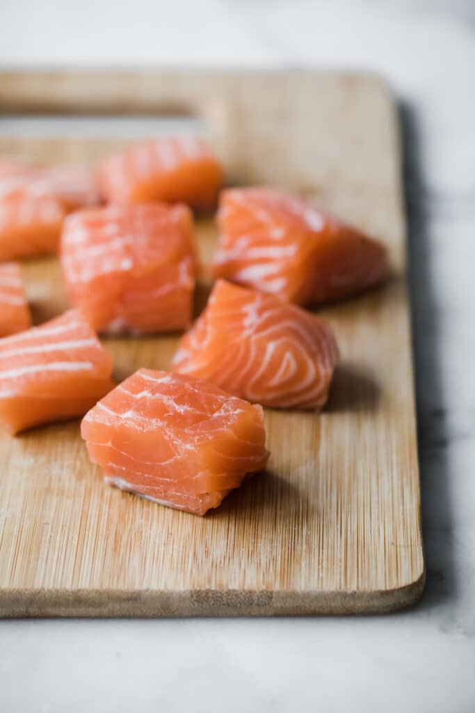 Salmon cut into 1x1 cubes on a chopping board atop a marble kitchen counter.