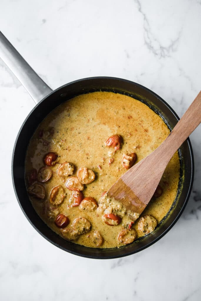Low-Carb curry paste with coconut milk and other ingredients being cooked on a pan.