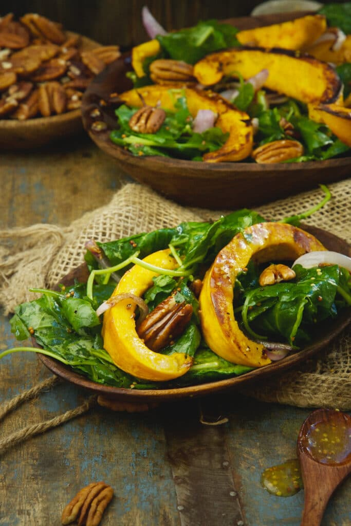 a whole serving of roasted pumpkin salad atop a wooden table