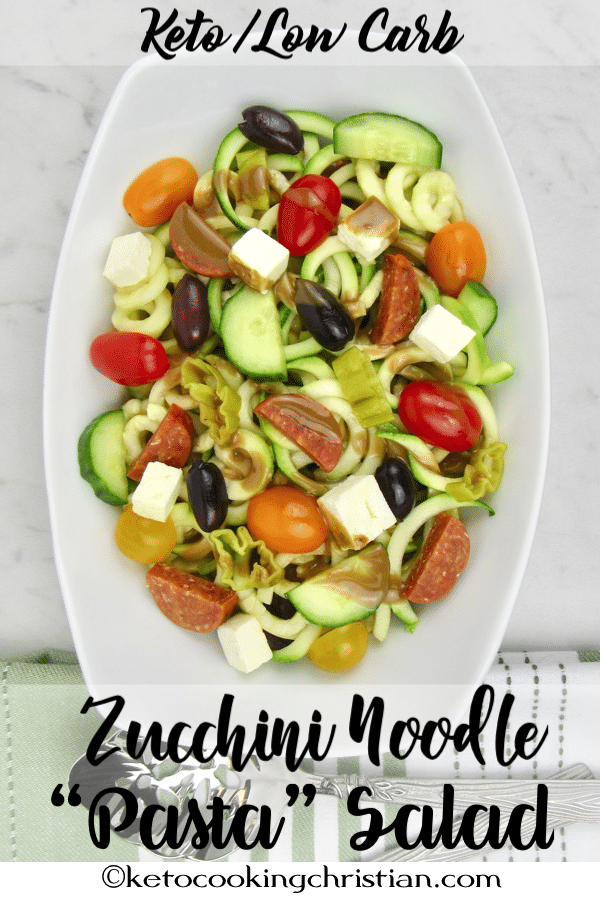 overhead shot of a plate of zucchini noodle pasta salad atop a marble kitchen counter