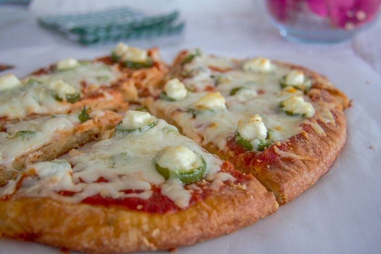 close-up angled shot of jalapeño popper pizza atop a marble kitchen counter