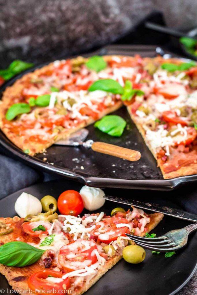 a slice of keto bacon fathead pizza with keto bacon fathead pizza on a pan in the background