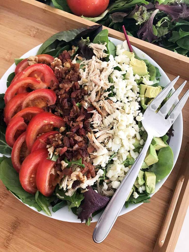 an angled shot of keto cobb salad on a plate with a fork atop a wooden kitchen counter
