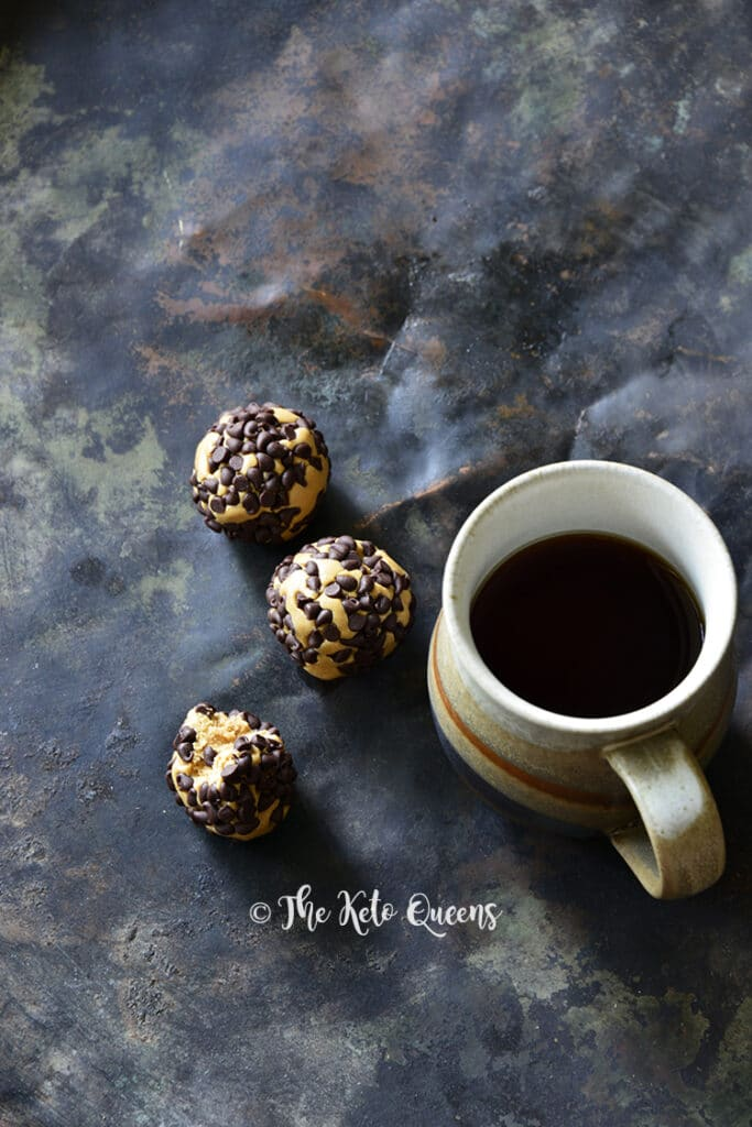 3 keto chocolate peanut butter protein bites with a cup of coffee on the side atop a marble kitchen counter