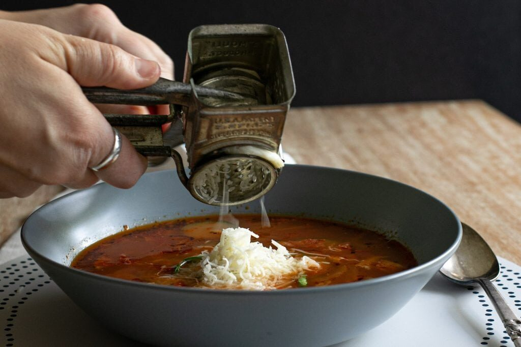 mozzarella cheese being topped on a bowl of pizza soup with zucchini atop a wooden table