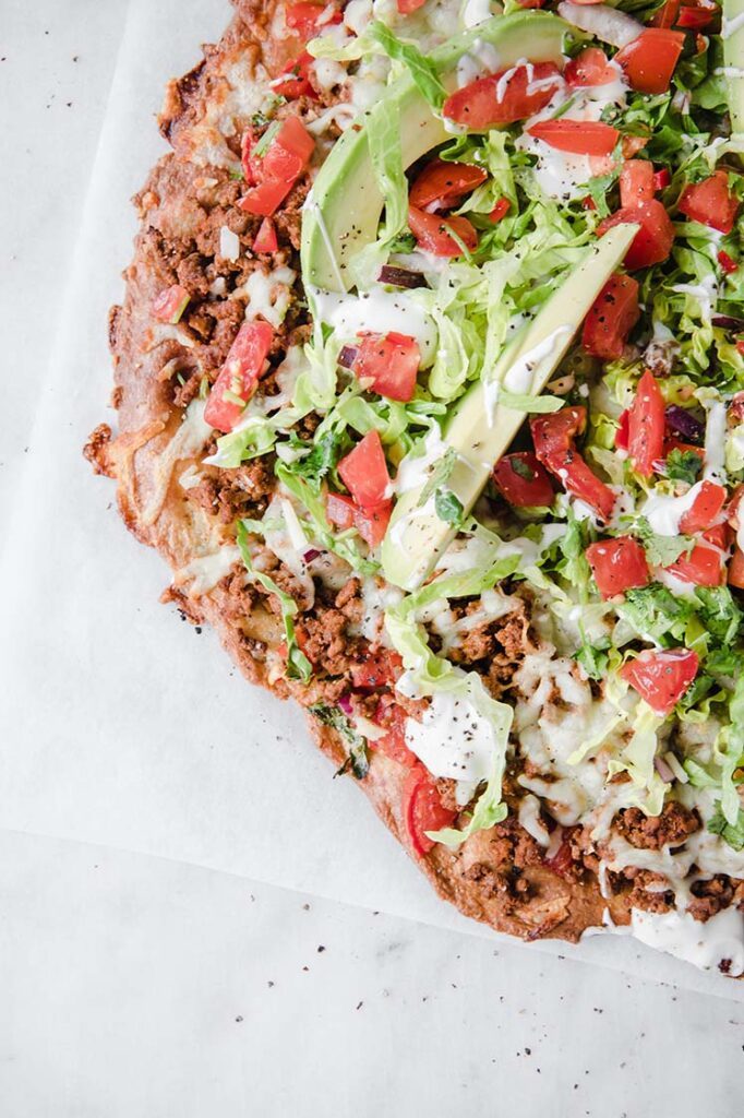 close up shot of ket fathead taco pizza atop a marble kitchen counter