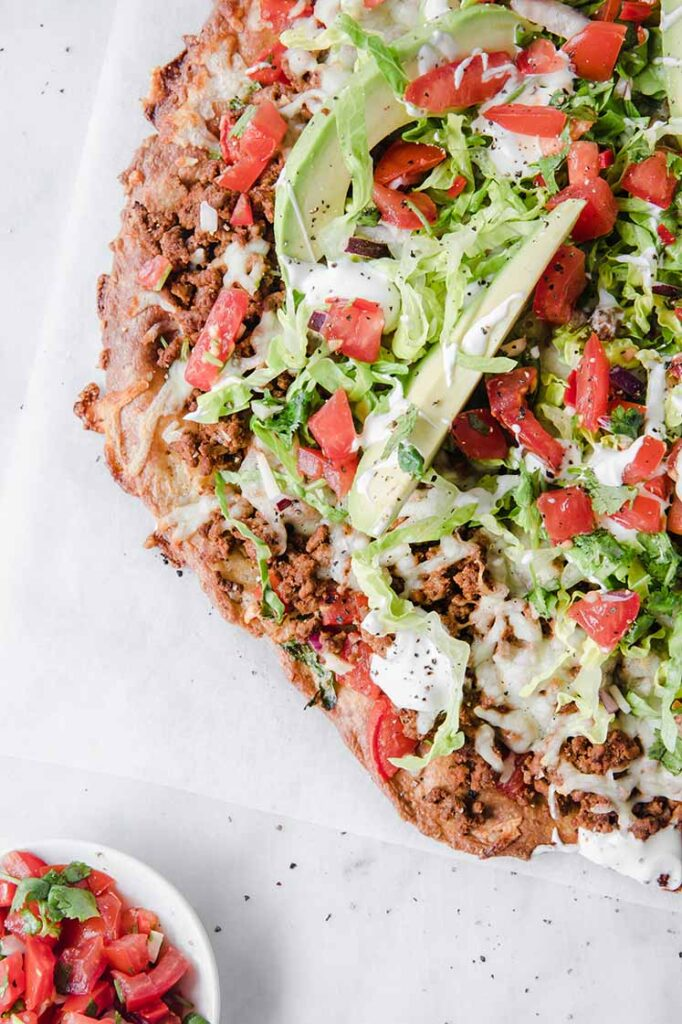 close up shot of Keto Fathead Taco Pizza with keto salsa at the bottom left corner marble kitchen counter
