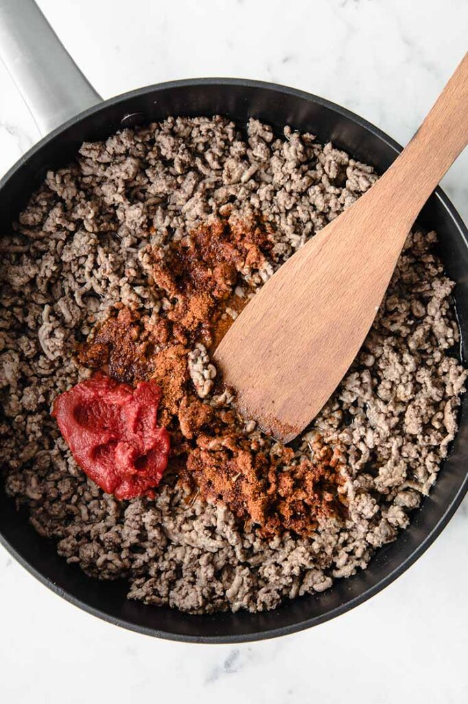 overhead shot of ground beef with taco spice and tomato paste being cooked in a pan with a wooden spatula at the side atop a marble kitchen counter
