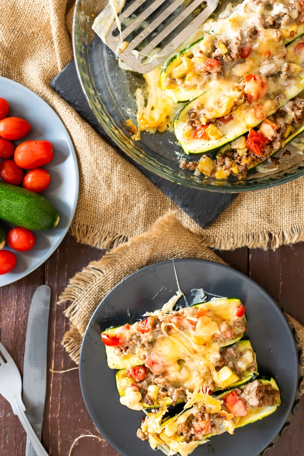 3 zucchini burrito boats on a plate with cherry tomatoes at the back ground atop a wooden table