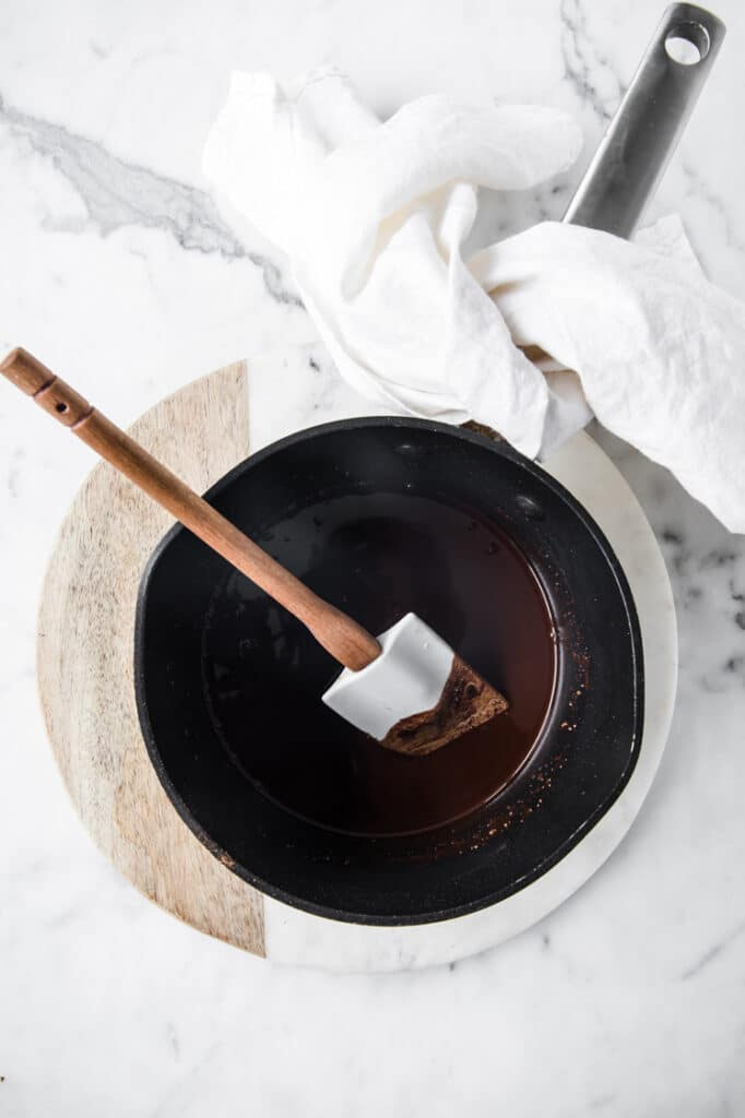 melted chocolate in saucepan with rubber spatula on white marble board next to white towel