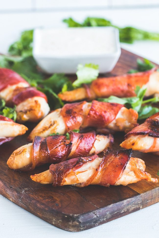 close-up shot of bacon wrapped chicken tenders on a wooden plate atop a marble kitchen table