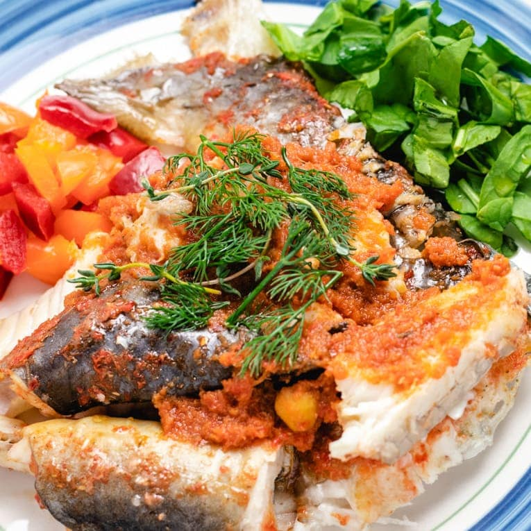 one plate of baked whole catfish garnished with herbs and spices