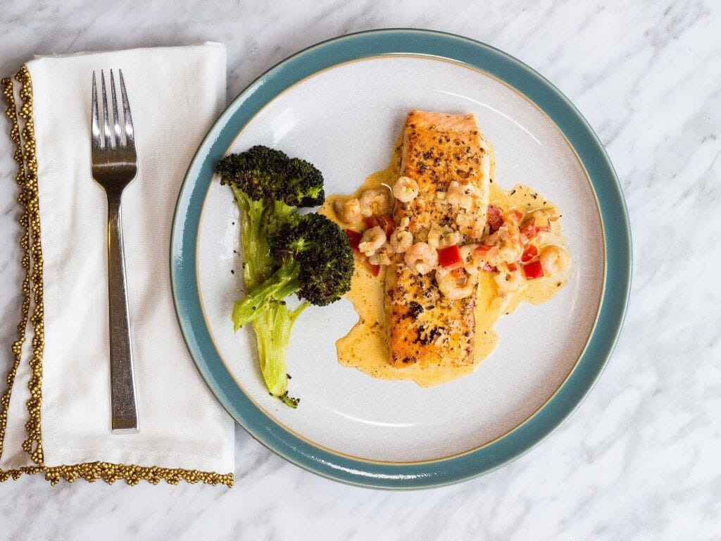 creamy cajun salmon with shrimp on a plate with broccoli on the side atop a marble kitchen counter