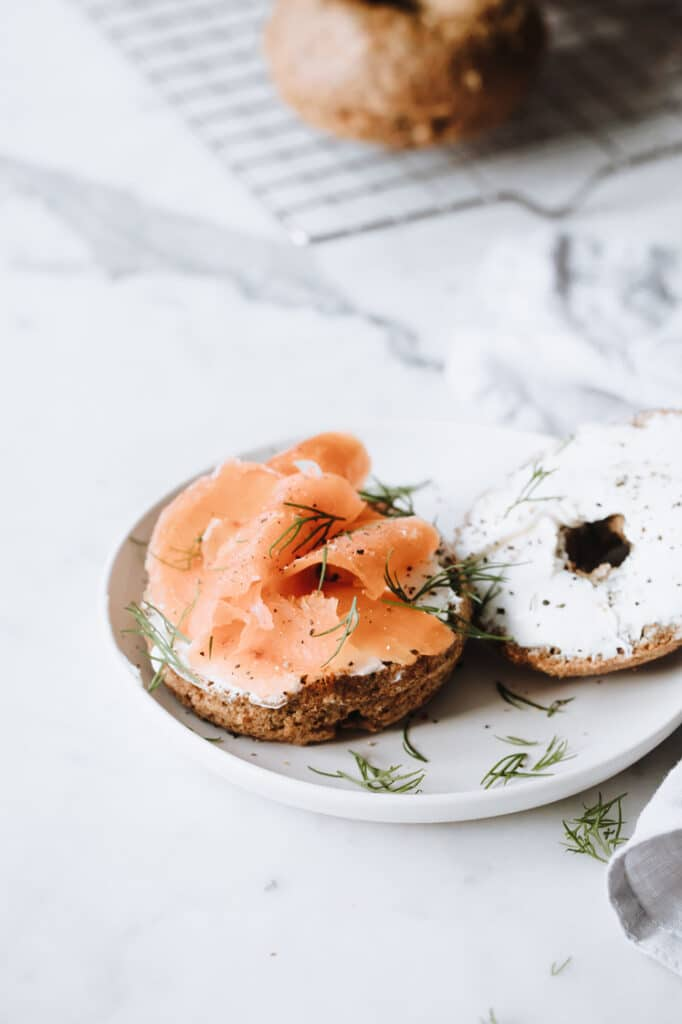 nut free keto bagels on a plate topped with cream cheese, lox, and fresh herbs