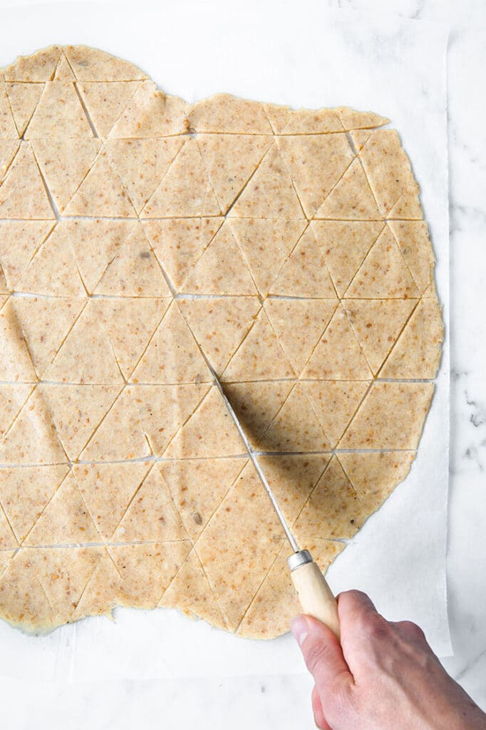 nut free keto nacho dough being cut by a knife on parchment paper