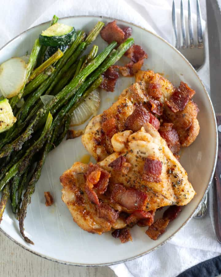 One-Skilletketo chicken with bacon on a plate with roasted asparagus