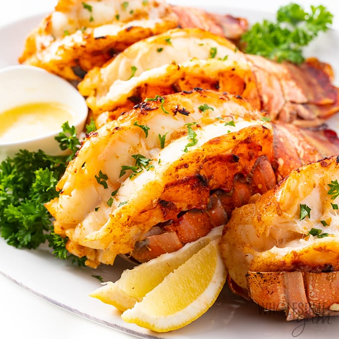a plate of broiled lobster tail garnished with lemons and herbs atop a marble table