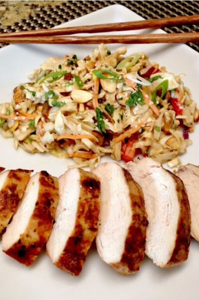 asian grilled chicken with peanut ginger slaw on a plate with chopsticks on the corner of the plate