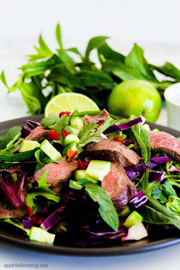 close-up shot of low carb thai beef on a plate atop a wooden table