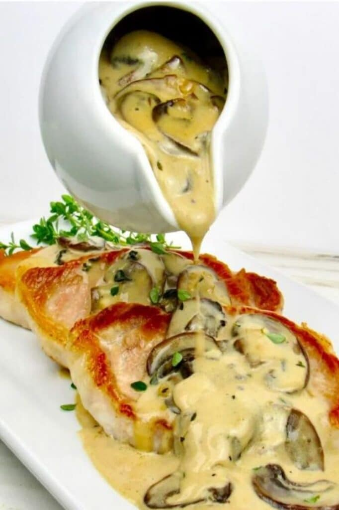 creamy mushroom gravy being poured on three slices of pork chop on a plate atop a marble kitchen table