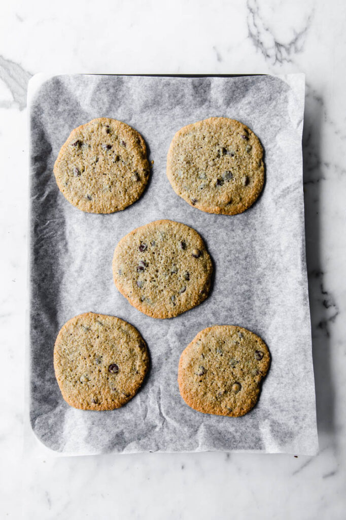 5 nut-free chocolate chip cookies on a baking sheet lined with parchment paper atop a marble kitchen table