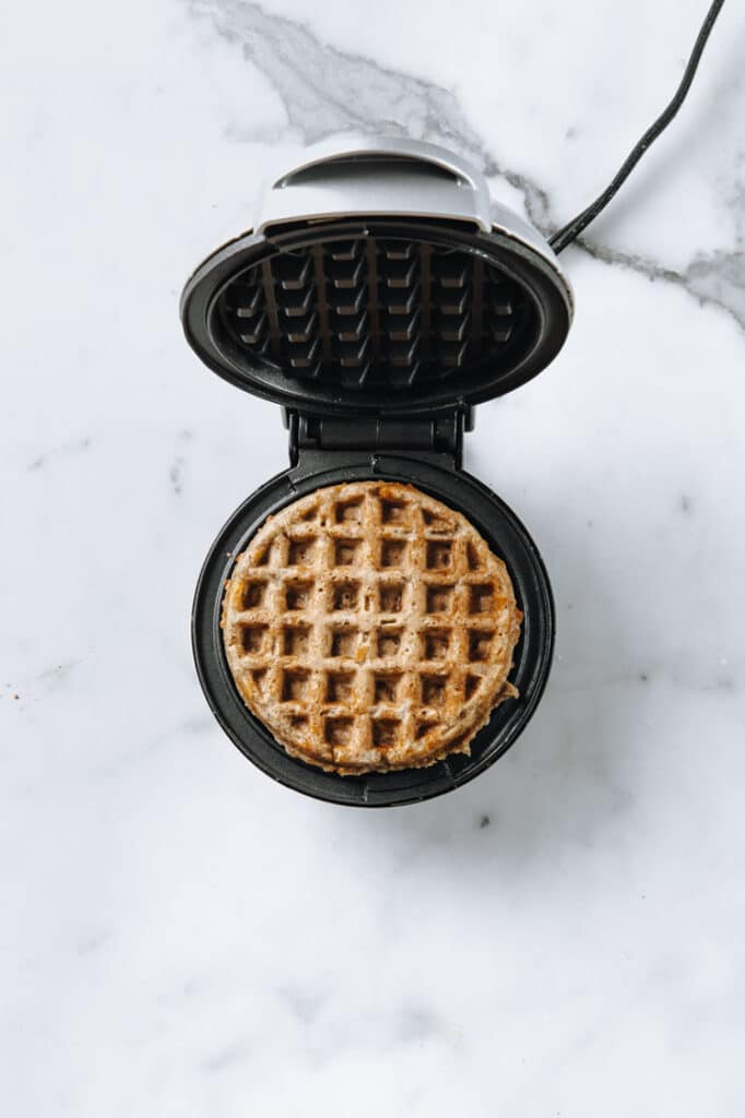 cinnamon roll chaffle batter baked in a waffle iron atop a marble kitchen counter