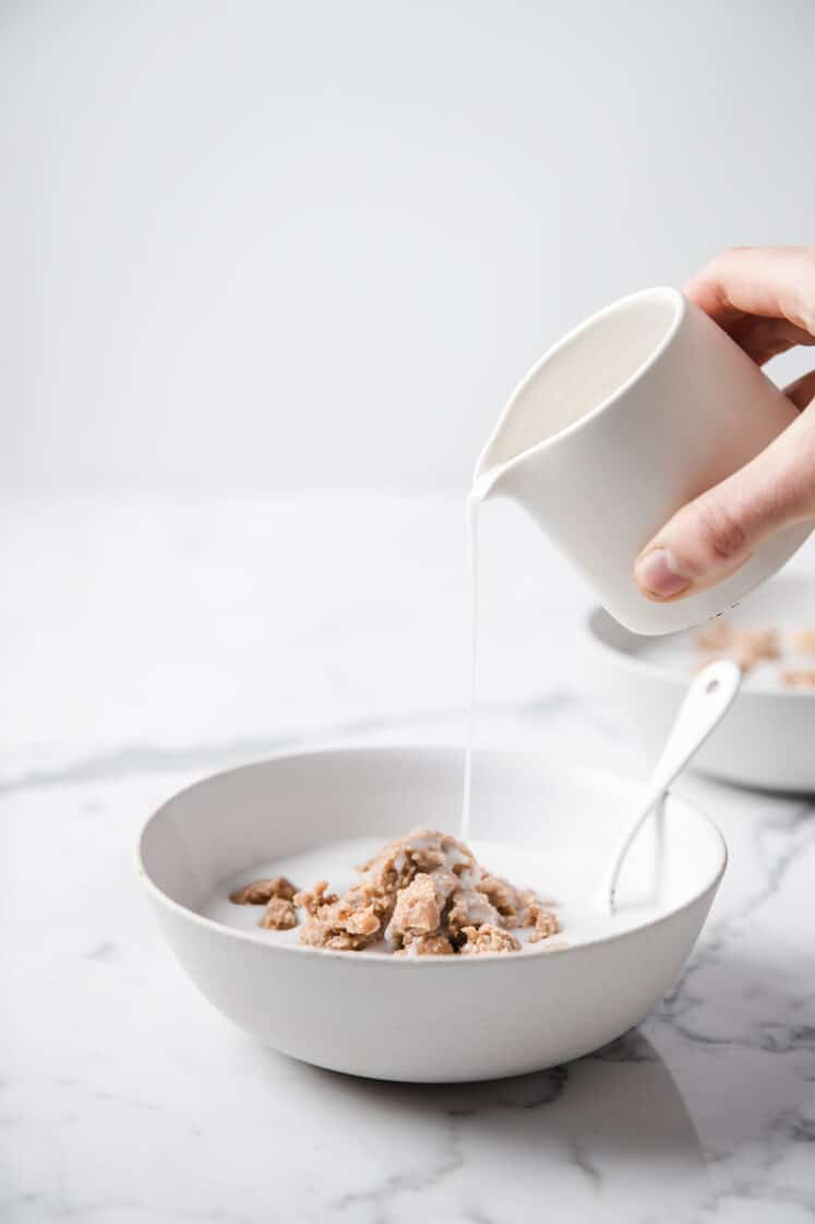 milk being poured on a bowl of Cinnamon Toast Crunch Cereal atop a marble kitchen table