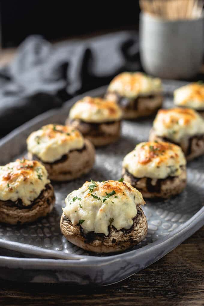 a tray full of crab stuffed mushrooms with cream cheese