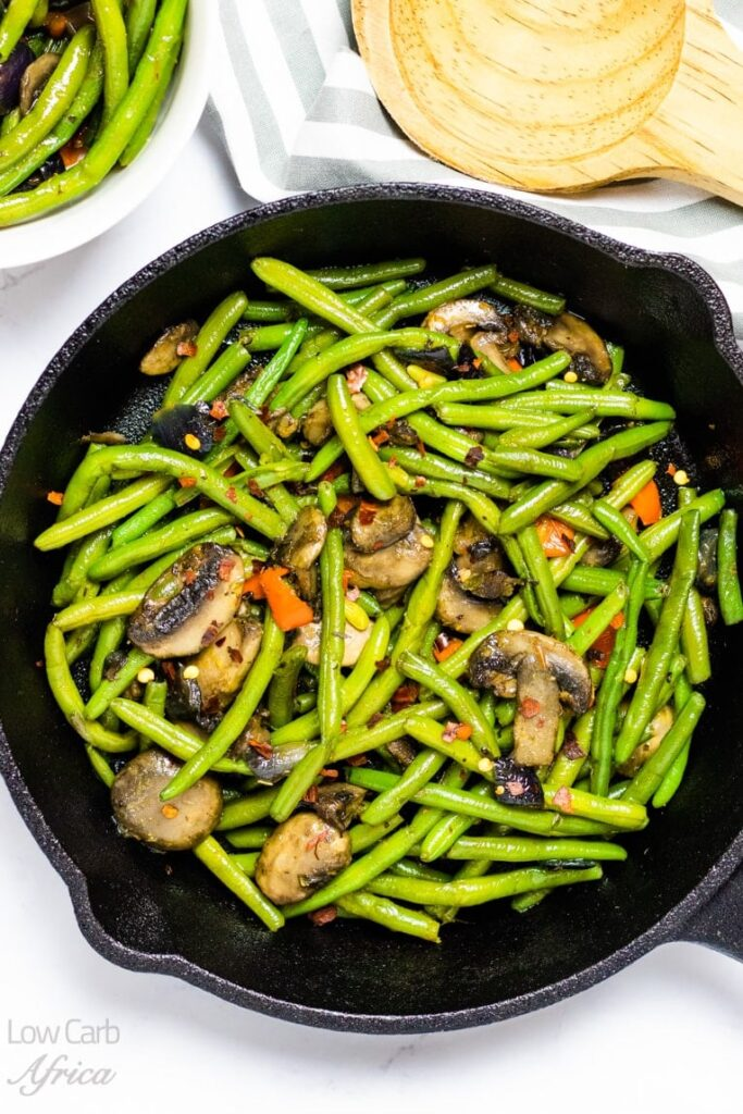 sauteed green beans and mushroom on a pan atop a marble kitchen table