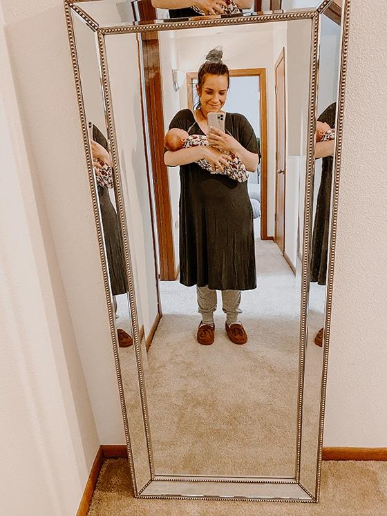 selfie in mirror of sara nelson holding newborn daughter during postpartum experience