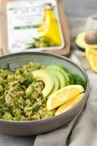avocado tuna salad in a bowl with sliced avocado and lemon wedges