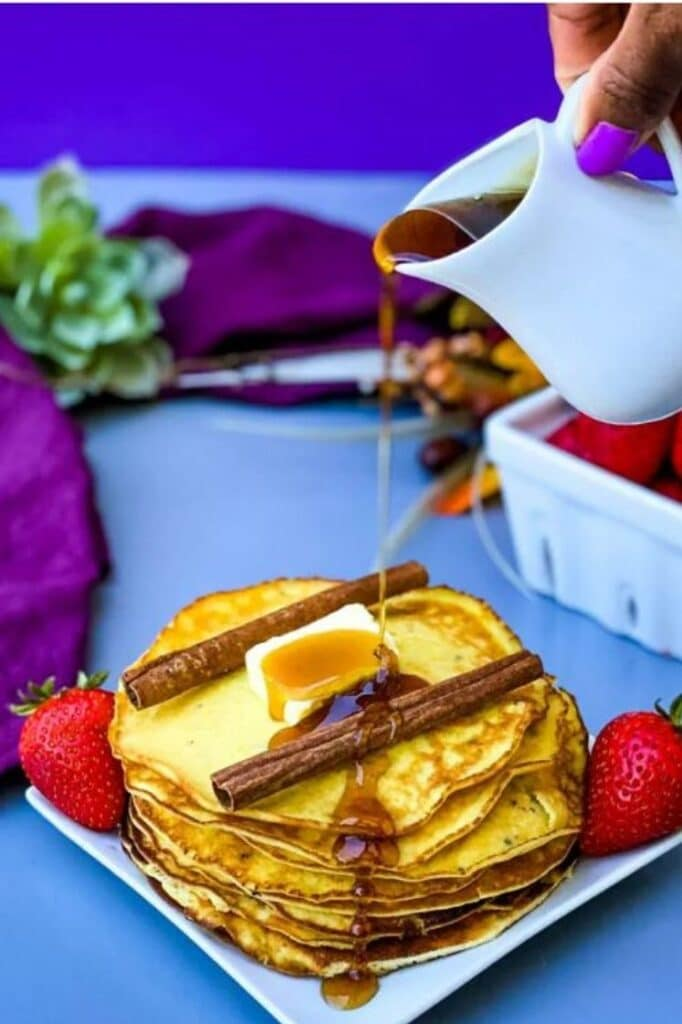 syrup being poured on top of cream cheese pancakes on a plate atop a blue table