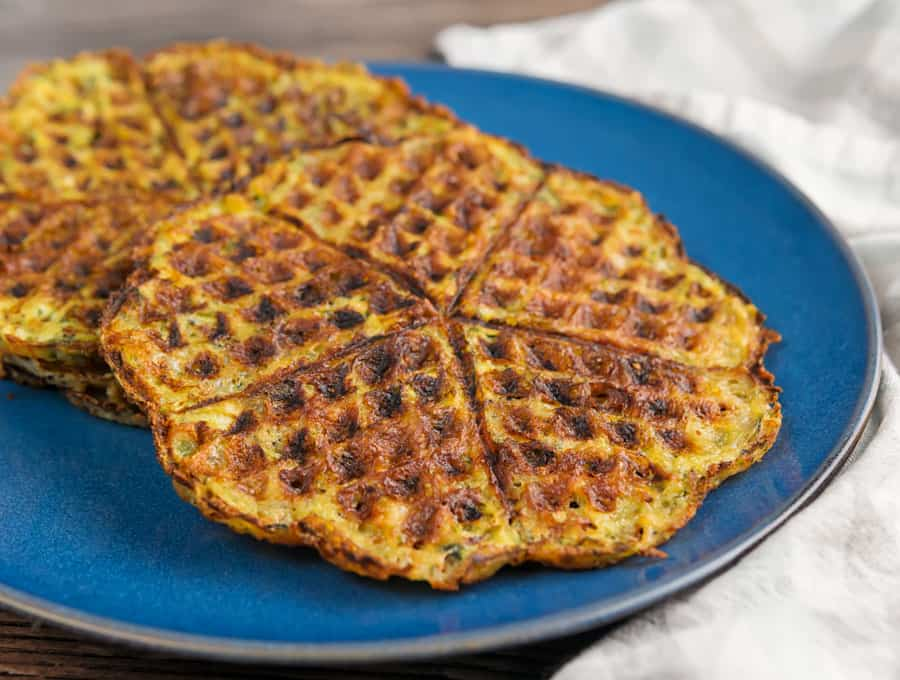 two zucchini chaffles on top of each other on a plate atop a marble table