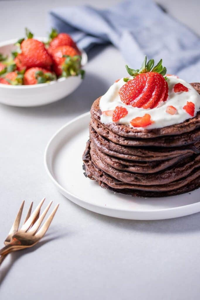 angled shot of chocolate protein pancakes on a plate topped with strawberries and cream