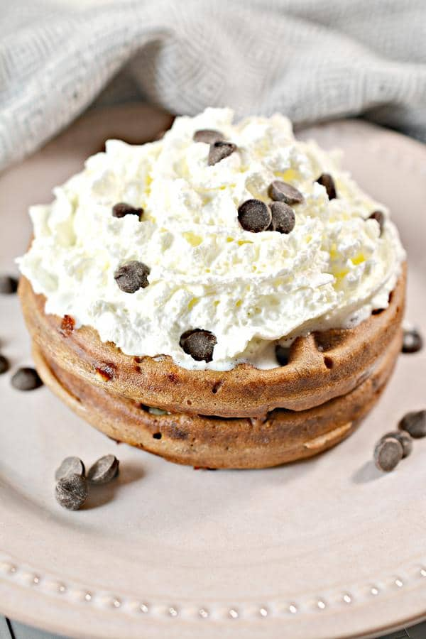 close-up shot of low carb peanut butter chocolate chaffle topped with whipped cream and chocolate chips