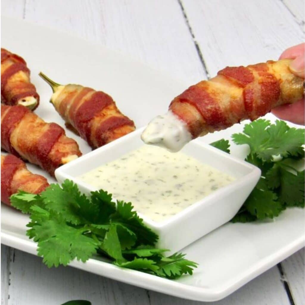 Air Fryer Bacon Wrapped Jalapeño Poppers on a plate atop a kitchen table