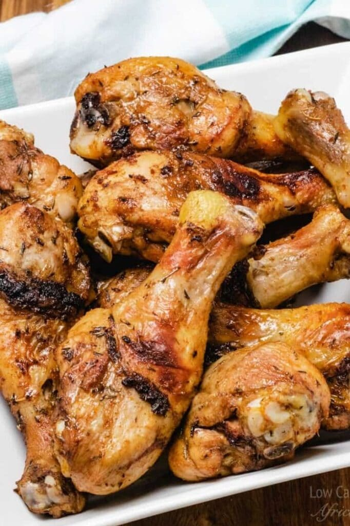 close-up image of crispy skin baked chicken drumsticks on a plate